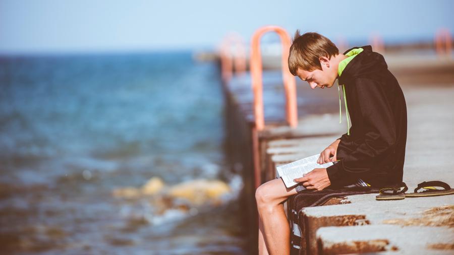 ung dreng sidder på en mole og læser