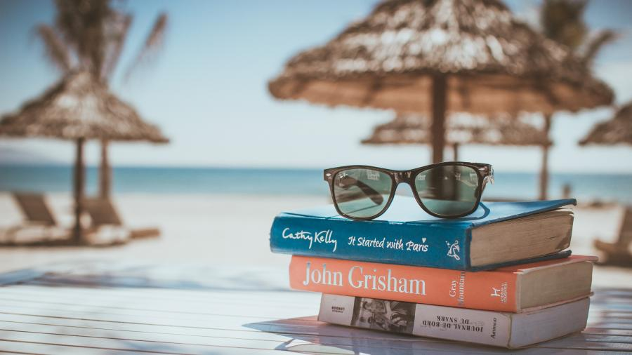 Bogstak og solbriller på en tropisk strand