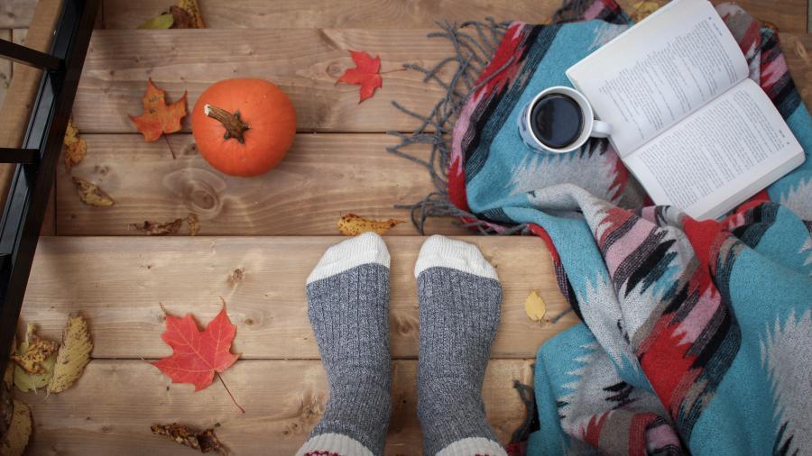 sokkeklædte fødder, en kop kaffe og en åben bog