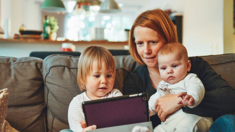 Kvinde og to små børn ser film på en ipad