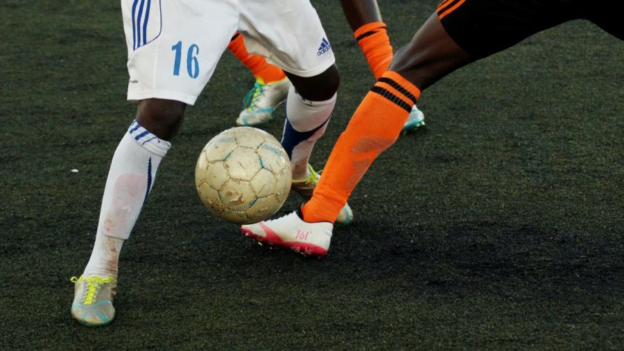 benene af fodboldspillere der kæmper om bolden