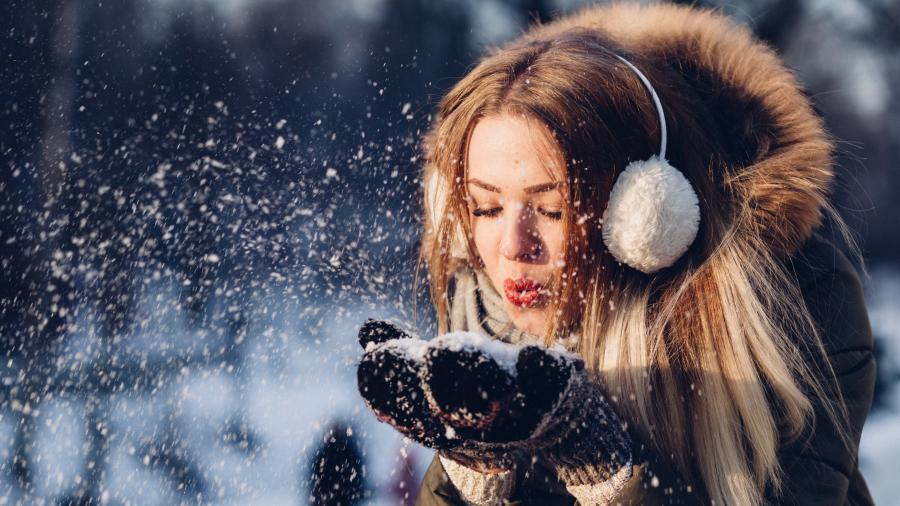 kvinde blæser sne ud af sine vanter