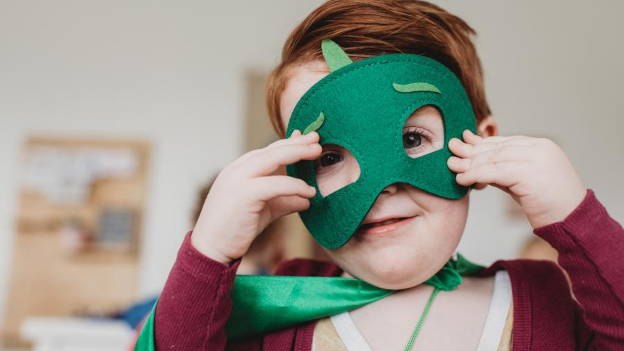 barn med grøn filt maske