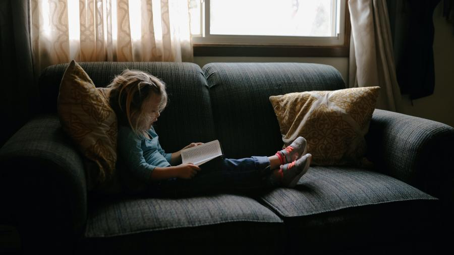 lille pige der læser i sofa