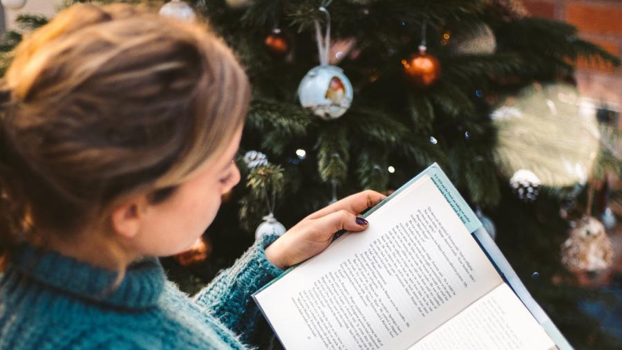 en kvinde der sidder foran et juletræ og læser i en bog
