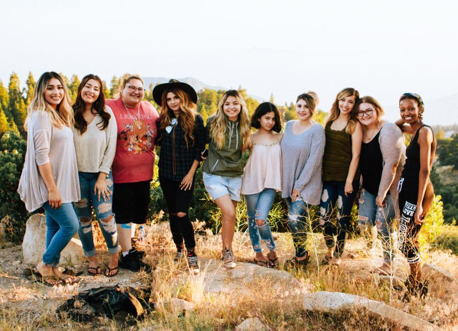 10 kvinder på en klippe med solen bag sig