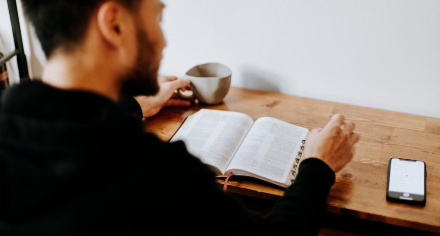 en mand der læser i en bog med en telefon liggende på bordet